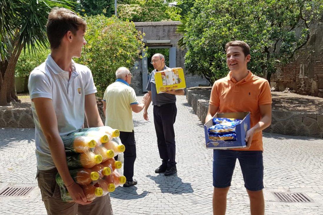 Due ragazzi aiutano un parroco gesuita a scaricare viveri per i poveri