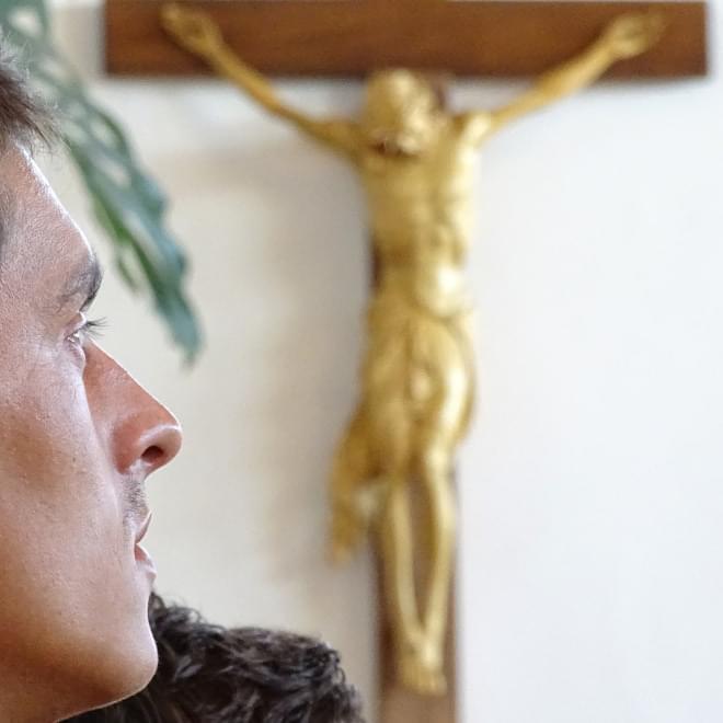 Un giovane in preghiera di fronte al Crocifisso